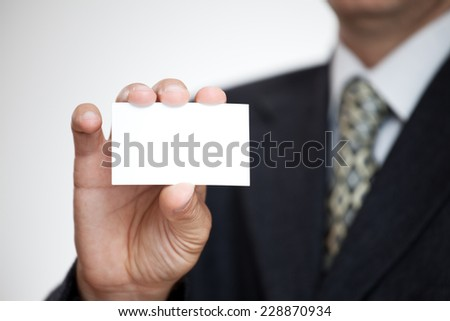 Businessman showing his business card. Shallow depth of field - focus on fingers and card. You can just add your text there. - stock photo