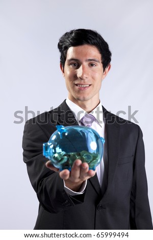 Businessman showing his business profit on a transparent piggy bank full of money (isolated on gray) - stock photo