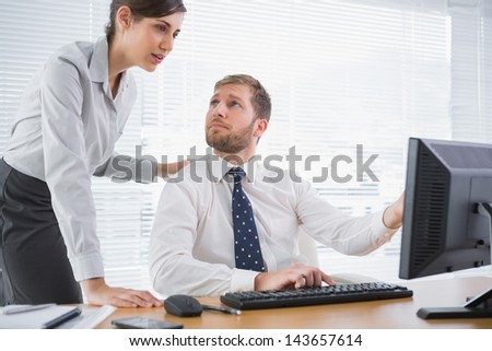 Businessman showing his co worker something on computer at his desk in office - stock photo