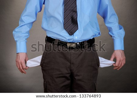 Businessman showing his empty pockets, on grey background