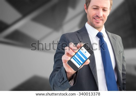 Businessman showing his smartphone screen against skyscraper - stock photo