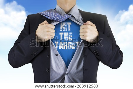 businessman showing Hit the target words underneath his shirt over blue sky - stock photo