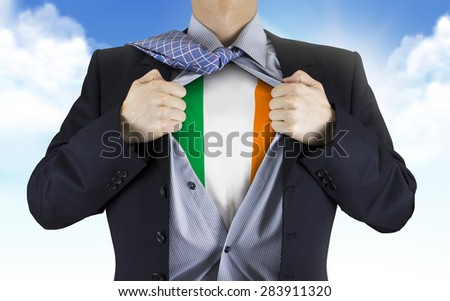 businessman showing Ireland flag underneath his shirt over blue sky - stock photo