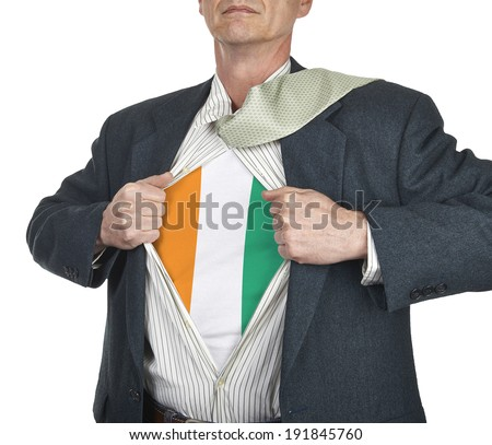 Businessman showing Ivory Coast flag superhero suit underneath his shirt standing against white background - stock photo
