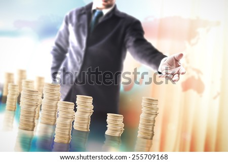 Businessman showing many golden coins over blurred office background. - stock photo