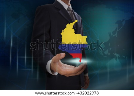 Businessman showing map of Colombia on globe background - stock photo