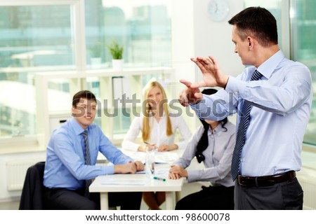 Businessman showing new device to his employees - stock photo