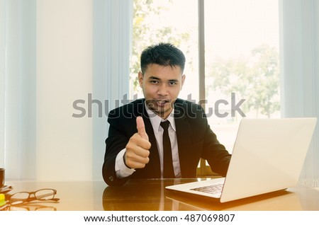 Businessman showing OK sign with his thumb up. Selective focus on face.