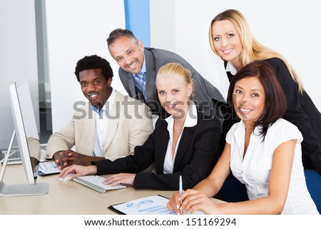 Businessman Showing On Computer To His Colleagues - stock photo