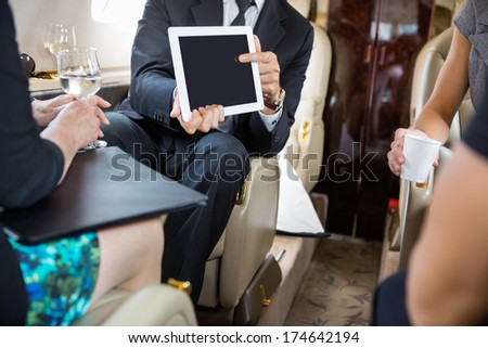 Businessman showing project on digital tablet to partners in private jet - stock photo