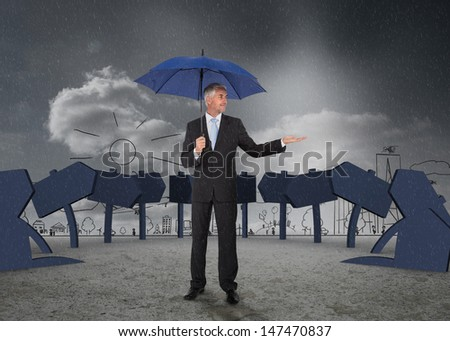 Businessman showing signs and a city and holding blue umbrella