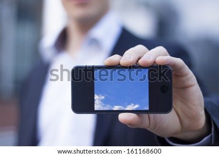 Businessman showing smartphone screen with office buildings in background - stock photo