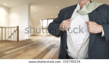 Businessman showing superhero suit underneath his shirt standing against clock with time for action - path for the shirt - stock photo