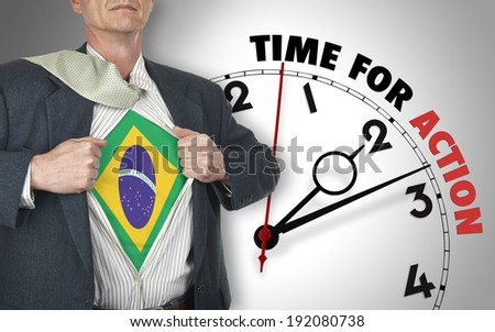 Businessman showing superhero suit with flag from Brazil underneath his shirt standing against clock with time for action - path for the shirt - stock photo