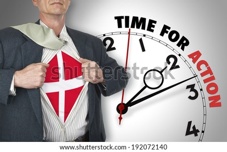 Businessman showing superhero suit with flag from Denmark underneath his shirt standing against clock with time for action - path for the shirt