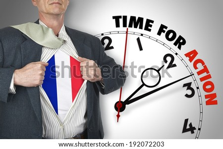 Businessman showing superhero suit with flag from French underneath his shirt standing against clock with time for action - path for the shirt