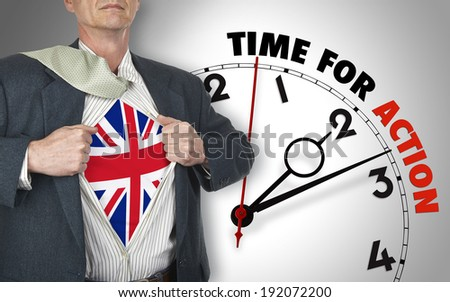 Businessman showing superhero suit with flag from UK underneath his shirt standing against clock with time for action - path for the shirt - stock photo
