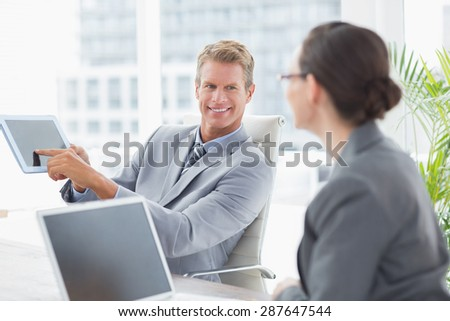 Businessman showing tablet at his colleague in an office - stock photo