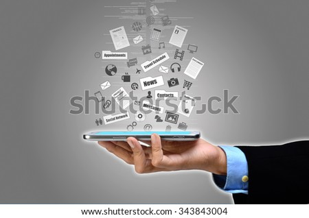Businessman showing the concept what he can do with the internet on his smart phone / tablet.