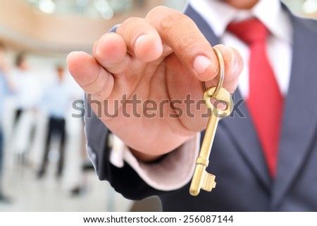 businessman showing the golden key to success - stock photo