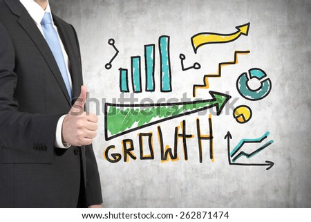 businessman showing thumb up and drawing charts on wall - stock photo