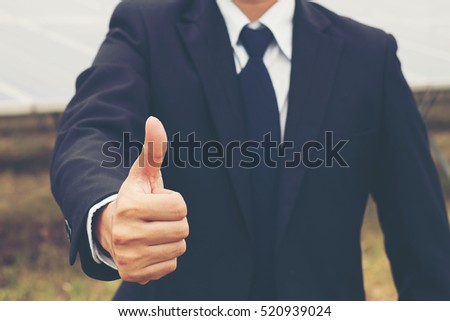 businessman showing thumbs up at solar power plant
