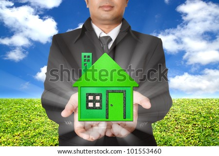 businessman shows a green house with blue sky