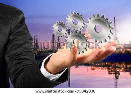 Businessman shows gear to success on industrial background - stock photo