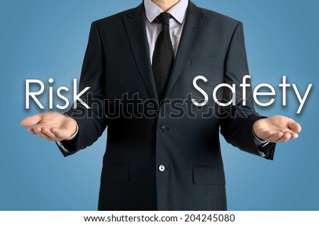 businessman shows two possibilities: risk or safety - stock photo
