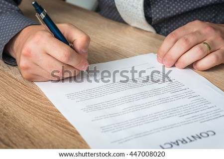 Businessman signing a contract to conclude a deal - business concept