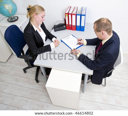 Businessman signing a contract with a obviously pleased looking businesswoman