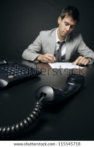 businessman signing a document, focus on telephone handset - stock photo