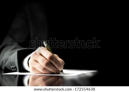 Businessman signing a document, taking notes, completing a questionnaire or writing correspondence, close up view of his hand and the paper - stock photo