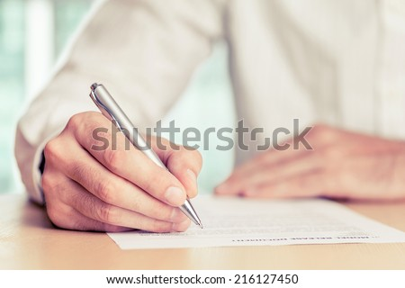 Businessman signing a document. Tinted photo, shallow depth of field. - stock photo