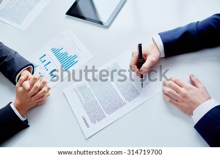Businessman signing contract after making agreement - stock photo