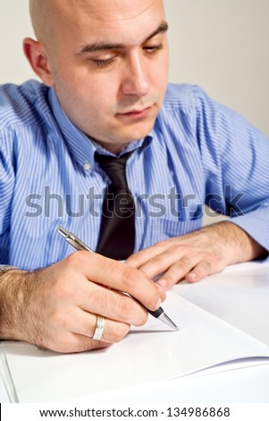 Businessman signing contract. Business man in blue shirt is signing agreement document. - stock photo