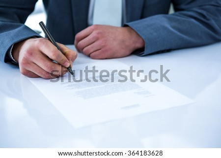 Businessman signing contract in a office - stock photo