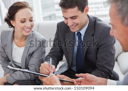 Businessman signing contract while his partner is looking at him in cosy meeting room - stock photo