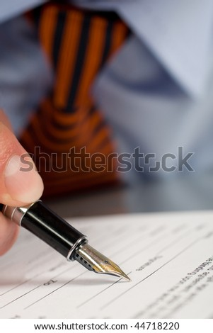 Businessman signing contract with pen - stock photo
