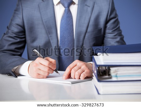 Businessman signing documents, blue background