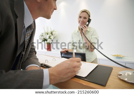 Businessman signing guestbook in reception area, female receptionist using telephone, smiling - stock photo