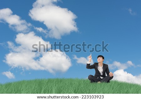 Businessman sit on grassland and finger toward the sky.