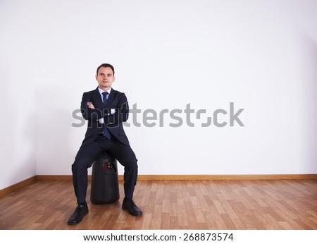 Businessman sit on his luggage - stock photo