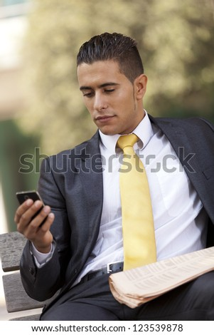 Businessman sited in a bench, sending short messages over his cellphone - stock photo