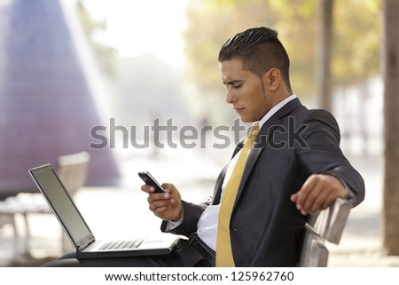 Businessman sited in a bench, sending short messages over his cellphone