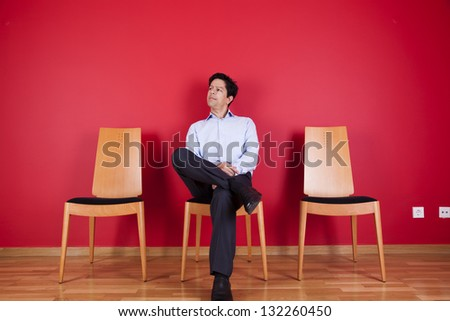 Businessman sited next to a red wall - stock photo