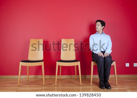 Businessman sited next to a red wall