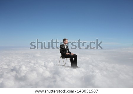 businessman sitting above the clouds