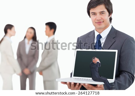Businessman sitting against salesman showing laptop screen with colleagues behind him - stock photo