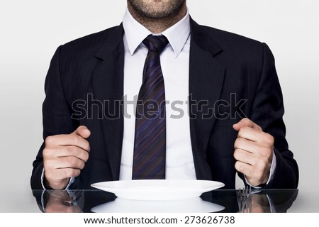 Businessman sitting and dining with an empty plate - stock photo